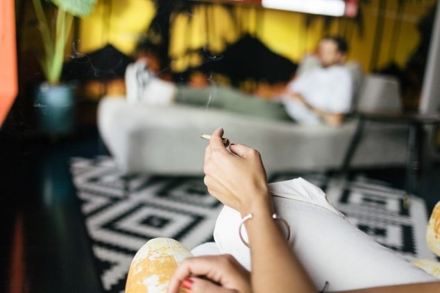 Cropped image of woman smoking while sitting against man on sofa at home
