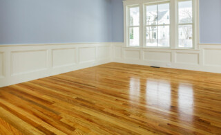 Hardwood floors in living room with a window and no furniture.