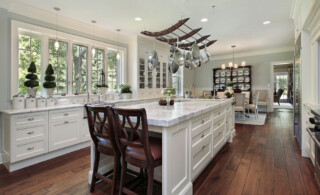 A bright kitchen with white marble countertops and wooden chairs.