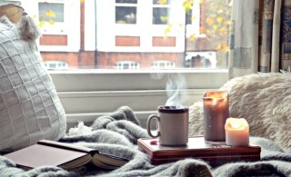 Cozy home. Candles, book and a cup of tea