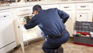 HVAC maintenance man works under the sink near the dishwasher.