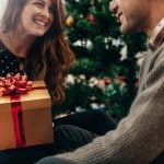Young couple celebrating Christmas by exchanging gifts.