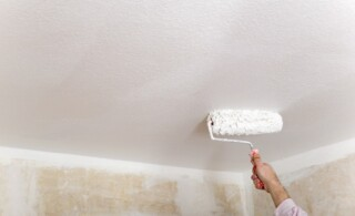 roller painting a popcorn ceiling
