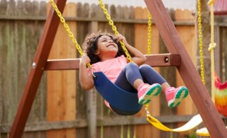 Kid toddler girl swinging on a playground swing