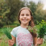Girl holding non-poisonous plants/herbs outside