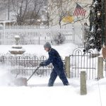 man uses a snow blower to remove snow from sidewalk