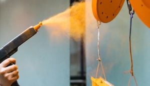 Powder coating of metal parts. A man in a protective suit sprays powder paint from a gun on metal products.