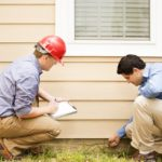 Repairmen, building inspectors, exterminators, engineers, insurance adjusters, or other blue collar workers examine a building/home's exterior wall and foundation. One wears a red hard hat and clear safety glasses and holds a clipboard. The other checks the foundation with tool.
