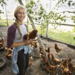 Smiling young female farmer holding chicken in chicken coop