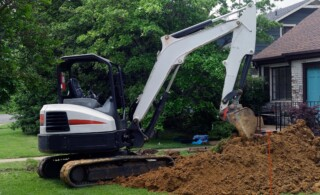 excavator in a front yard
