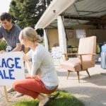 Couple putting up garage sale sign in yard