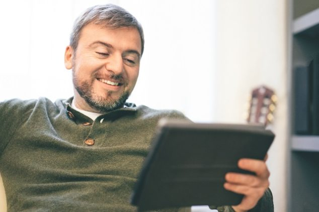 Man using digital smart home tablet on the couch