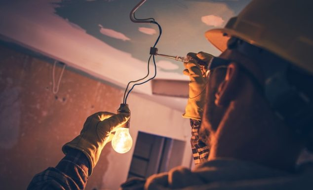 electrician repairing wiring for lighting in home