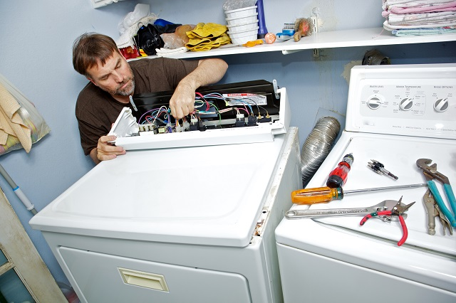 Appliance repair man fixing a clothes dryer