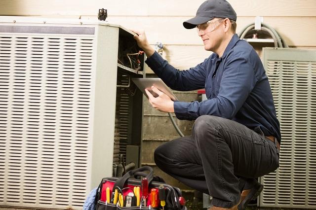 HVAC repair man working on an exterior AC unit