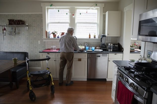 Senior man doing dishes in his kitchen with his walker