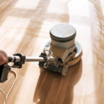 man buffer cleans laminate flooring