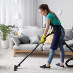 professional maid vacuuming a carpet