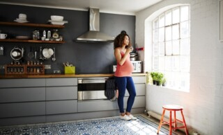 Pregnant woman in tidy modern kitchen in a renovated old building