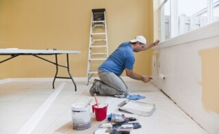 Man painting wall with roller in the house