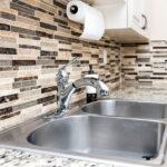 stainless steel sink in kitchen with backsplash