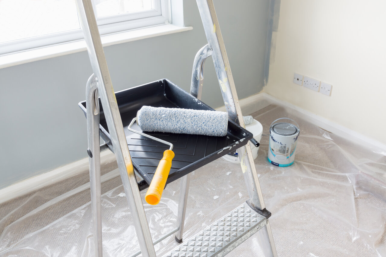 paint roller resting on tray on ladder