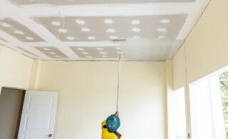 professional painter using roller on ceiling