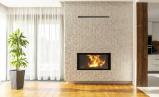Fireplace on brick wall in bright living room interior of house with plant and windows