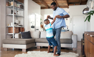 Father and son dancing in living room