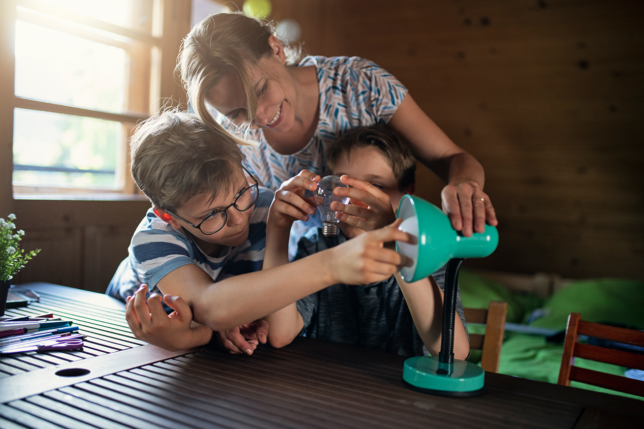 Mother and children using energy efficient light bulb
