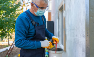 man painting home exterior