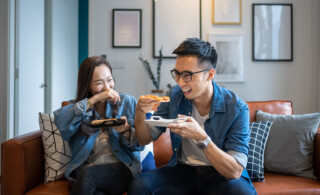 couple eating pizza on couch