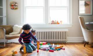Two children play on wooden floor with colorful toys in front of white radiator