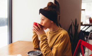 woman sipping coffee and looking out the window